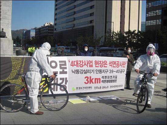 25일 서울 광화문 광장에서 환경보건시민센터 회원들이 방진복 차림에 방독면을 쓰고 4대강 자전거 길을 달리는 퍼포먼스를 하고 있다.