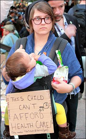 '월스트리트 점령' 시위가 벌어지고 있는 뉴욕 맨해튼 자유광장(주코티파크) 앞에서 한 아이의 어머니가 '(복지 예산 축소로) 아이의 의료비를 감당할 여력이 없다'는 내용의 손팻말을 들고 서 있다.