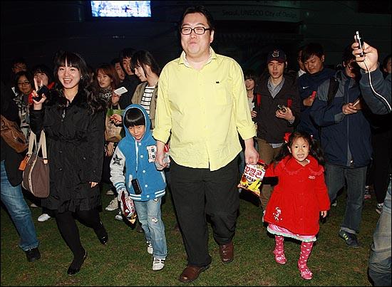 인터넷 시사라디오 '나는 꼼수다'의 김용민 평론가가 26일 저녁 서울시청광장에서 시민으로부터 선물받은 꼬깔콘을 아이에게 건네주고 함께 손을 잡고 사인회장으로 이동하고 있다.