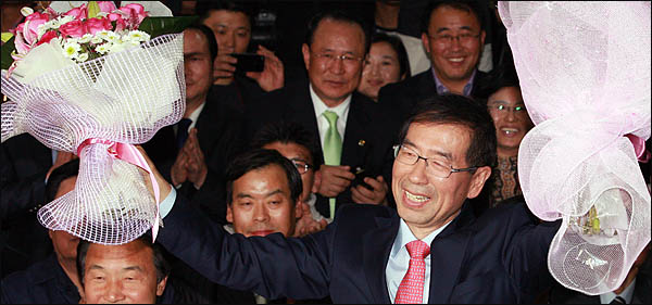 박원순 서울시장 당선자가 27일 새벽 안국동 선거캠프에서 승리를 자축하며 꽃다발을 받아들고 있다.