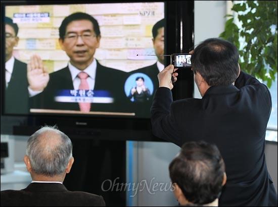 16일 오전 서울시청 별관 1층 로비에 설치된 TV를 통해 '박원순 서울특별시장 온라인 취임식'이 생중계되는 가운데 한 시민이 휴대폰으로 생중계 화면을 촬영하고 있다.