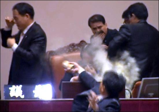 민주노동당 김선동 의원이 22일 오후 여당의 한미FTA(자유무역협정) 비준안 강행처리를 저지하기 위해 본회의장 발언대에 올라가 사과탄으로 알려진 최루탄을 의장석에 앉아 있던 정의화 국회부의장 앞에서 터뜨리고 있다.