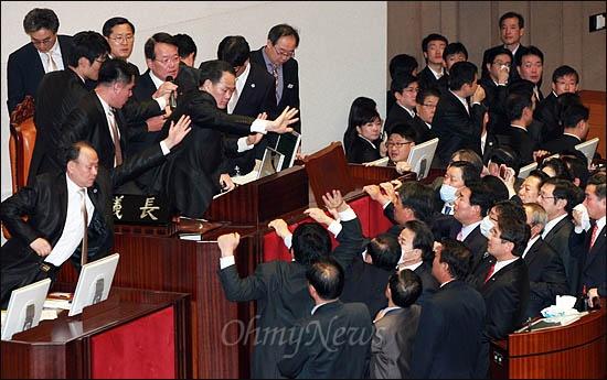 22일 국회 본회의에서 정의화 부의장이 한미FTA 비준안 통과를 선언하자 김선동 민주노동당 의원 등 야당 의원들이 의장석을 에워싼 채 항의하며 '무효'를 주장하고 있다.