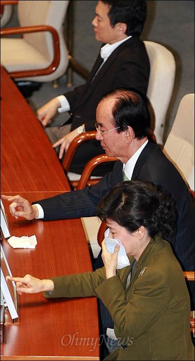 한나라당 박근혜 전 대표가 22일 최루 가루가 살포된 국회 본회의장에서 마스크를 쓴 채 한미FTA 비준안 표결에 참여하고 있다. 맨 위는 남경필 외통위원장.