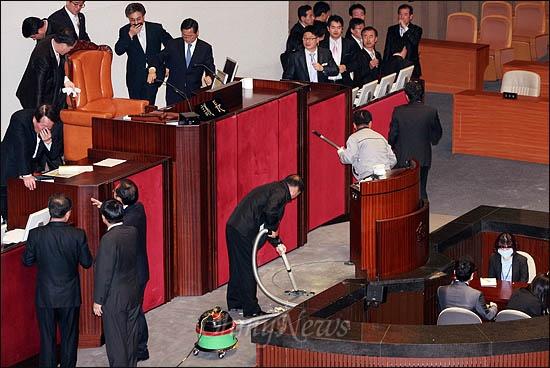 한미FTA 비준안 강행처리를 저지하기 위해 김선동 민주노동당 의원은 22일 국회 본회의장에 최루 가루를 살포했다. 아수라장이 된 국회 본회의장 의장석을 직원들이 황급히 치우고 있다.