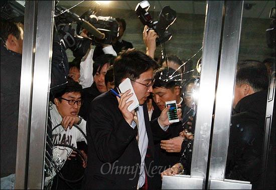 한미FTA 비준안 강행처리를 위해 한나라당 의원들이 22일 국회 본회의장에 입장한 가운데, 국회 경위들이 취재진의 방청석 출입까지 막고 나서 호된 항의를 받았다. 야당 당직자들이 깨부순 유리문 파편 사이로 기자들이 진입을 시도하고 있다.