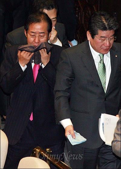 한나라당 홍준표 대표가 22일 최루 가루가 살포된 국회 본회의장에서 한미FTA 비준안을 통과시킨 뒤 매캐한 회의장을 뜨고 있다.