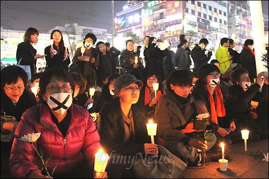 지난 1일 새벽 창원 한 모텔에서 성구매 남성한테 피살당한 노래방 도우미를 기리는 촛불추모문화제가 29일 저녁 창원 상남동 분수광장에서 열렸다. 참가자들이 마스크를 한 채 국화꽃과 촛불을 들고 앉아 있다.