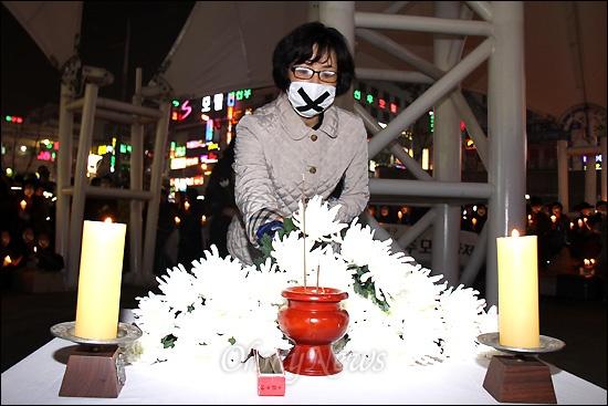 지난 1일 새벽 창원 한 모텔에서 성구매 남성한테 피살당한 노래방 도우미를 기리는 촛불추모문화제가 29일 저녁 창원 상남동 분수광장에서 열렸다. 사진은 헌화하는 모습.