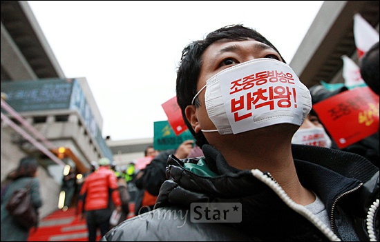 """종합편성채널인 채널A(동아일보), TV조선(조선일보), jTBC(중앙일보), MBN(매일경제) 4사 공동 개국 축하행사가 세종문화회관에서 열린 1일 오후, 행사장 앞에서 열린 언론노조 규탄집회에서 한 언론노조 조합원이 """"조중동 방송은 반칙왕""""이라는 글자가 적힌 마스크를 쓴채 종편출범을 규탄하고 있다."""