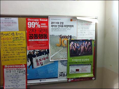 서울을 점령하라  12월 12일(월)에 촬영한 학교 자유게시판이다. '서울을 점령하라' 2차 공동행동 포스터 옆엔 기업의 이미지 광고나 학원 광고 포스터들이 버젓이 붙어 있다. 이들 중엔 담당부서의 확인 도장이 찍혀 있는 것도 있다.