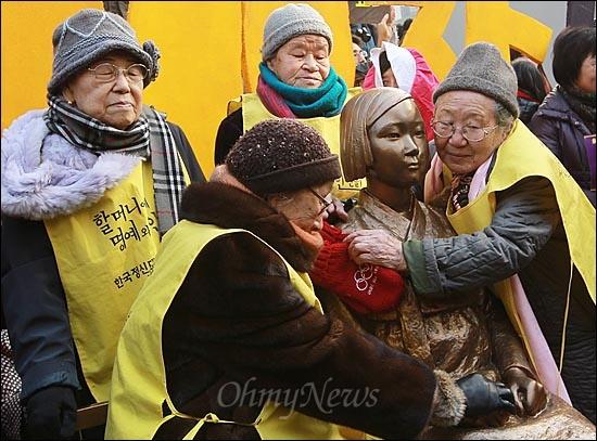 1천번째 수요시위 '나 어릴적 모습같아...' 14일 오후 서울 종로구 주한 일본대사관 앞에서 열린 '제1000차 일본군 위안부 문제 해결을 위한 정기 수요집회'에서 위안부 피해 김순옥(90, 사진 맨 왼쪽 시계방향), 박옥선(88), 길원옥(84), 김복동(85)할머니들이 시민사회의 모금으로 건립한 평화비를 안아보고 있다. 평화비는 한복을 입고 손을 무릎 위에 모은 채 작은 의자에 앉아 있는 10대 소녀의 모습을 형상화한 높이 130cm의 비로 할머니들이 항상 시위하던 일본대사관 정문에서 불과 15m 떨어진 건너편 인도에 설치됐다.