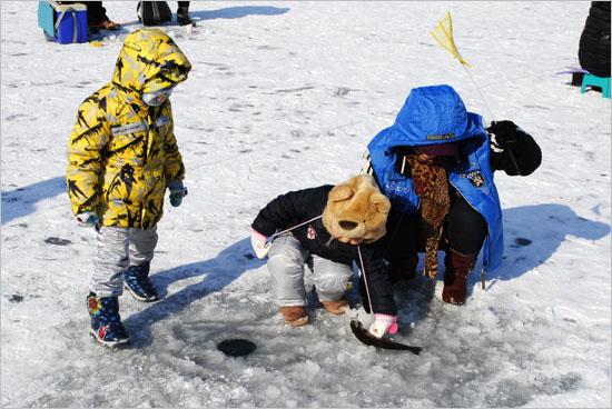 얼음 밖으로 나온 송어가 신기한 듯 내려다보는 아이들.