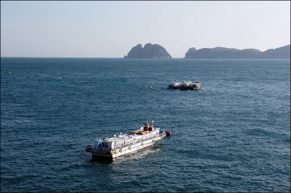 해금강 여행자를 외도에 내려 놓은 유람선은 바다 위에 떠 휴식을 취하고 있다. 뒤로는 해금강이 보인다.