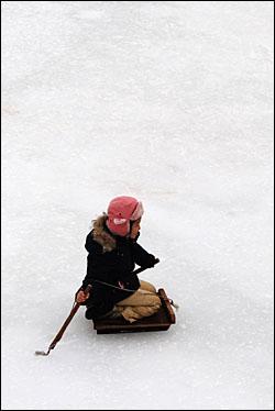 혼자서 썰매를 타고 얼음을 지치는 아이.