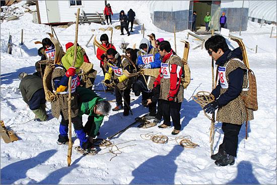 전국전통썰매대회에 들어가기 앞서 설피 매는 법과 발썰매 타는 법을 가르쳐주는 눈꽃마을 최종근 이장. 발썰매를 등에 매고 전통 사냥꾼 복장을 한 선수들이 이색적이다.