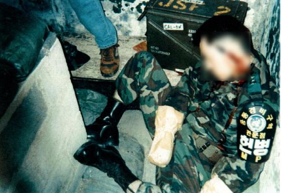 미군 수사관이 현장에서 촬영한 고 김훈 중위의 시신. 좌측 상단 청바지 차림의 미군 수사관 다리가 보이고 김 중위의 양 손에는 화약 잔재를 채취하기 위해 봉투가 끼워져 있다. (유족의 양해를 얻어 김 중위의 사진을 공개합니다)
