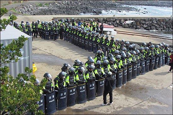 """해군의 구럼비 폭파 강행을 앞둔 강정마을의 현재 분위기는 """"거의 계엄 상황""""이라고 주민들은 전하고 있다. 공사를 감시하는 주민들이 바다로 나가게 못하도록 경찰이 강정포구를 에워싸고 있다."""