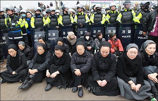 해군이 구럼비 바위 지역의 발파를 시작한 7일 오후 제주도 서귀포시 강정마을 해군기지 정문 앞에서 천주교 수녀님들과 마을 주민들이 해군기지 건설 중단을 촉구하며 연좌농성을 벌이고 있다.