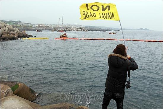 해군이 구럼비 바위 지역의 발파를 시작한 7일 오전 제주도 서귀포시 강정포구에서 한 시민이 해군기지 건설 중단을 요구하며 깃발을 흔들어 보이고 있다.