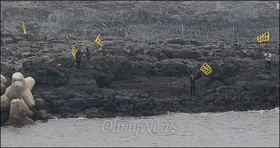 시민사회단체 활동가들이 7일 오후 제주도 서귀포시 강정마을 해군기지 건설현장에 카약을 타고 구럼비 바위 진입에 성공한 뒤 해군기지 반대하는 깃발을 들어보이고 있다.