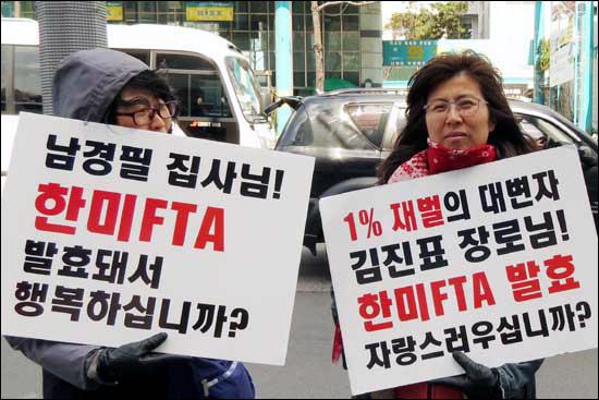 """다산인권센터 박진 상임활동가(오른쪽)가 """"1% 재벌의 대변자 김진표 장로님! 한미FTA 발효 자랑스러우십니까?""""라고 적힌 손팻말을 들고 서 있다."""