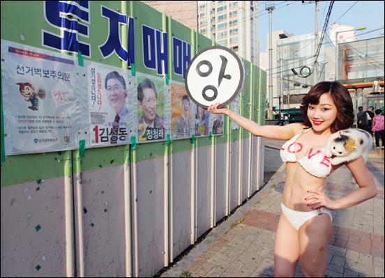 총선 공보물 앞에서 퍼포먼스를 벌인 낸시랭. 인터넷 상에서 공방을 벌였던 강용석 의원의 얼굴은 절묘하게 가리는 센스를 발휘했다.