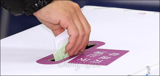 제19대 국회의원선거일인 11일 서울 종로구에 마련된 투표소에서 한 유권자가 투표하고 있다.