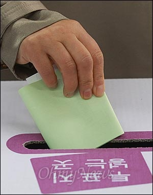 제19대 국회의원 선거날인 11일 오전 서울 마포구 공덕동 주민센터에 마련된 제4투표소에서 유권자가 기표용지를 투표함에 넣고 있다.