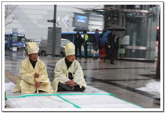 비를 맞고 앉아 있는 상주들 비를 맞고 앉아 잇는 상주들 뒤로 사복을 입은 경찰이 보인다. 해고노동자라는 이유로  감시와 처벌의 요주의 인물이 되어 버렸다.
