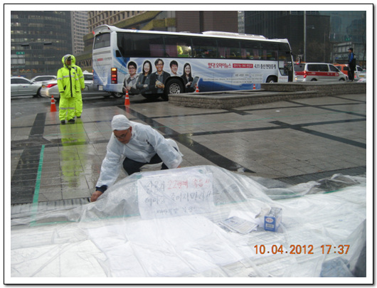 김정우 지부장 김정우 지부장이 비닐로 '쌍차 22번째 죽음!! 더 이상 죽이지 마라!!'는 종이를 비닐로 덮고 있다.