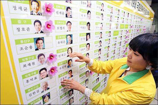 제19대 국회의원선거 개표가 진행중인 11일 밤 민주통합당 당사에 마련된 개표상황실에서 한 당직자가 당선이 확정된 후보 이름에 꽃을 달고 있다.