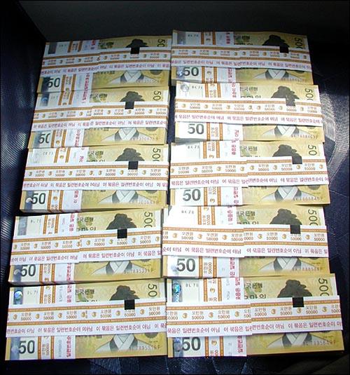<오마이뉴스>가 12일 농협 청와대지점에서 인출한 5천만 원 관봉. 5만원 신권 100장을 묶은 십자 띠지 위에 '이 묶음은 일련번호 순이 아님'이라고 표시돼 있다.