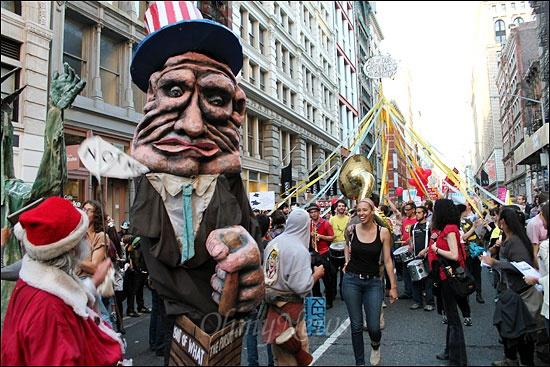 지난 1일(현지시간) 메이데이(노동절)을 맞아 미국 뉴욕 맨해튼에서 월가 점거 시위대, 노조, 이민자단체 등이 거리 행진을 벌였다. 미국 자본주의의 상징인 '엉클 샘' 대형 인형과 메이데이의 상징인 메이폴이 행진하고 있다.