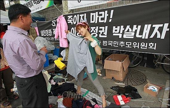 11일 오후 서울 중구 대한문 앞에서 열린 '쌍용자동차 희생자들을 돕기위한 후원 바자회'에서 한 자원봉사자가 시민들에게 기증된 물품을 보여주며 판매하고 있다.