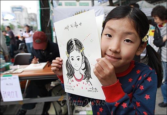 11일 오후 서울 중구 대한문 앞에서 열린 '쌍용자동차 희생자들을 돕기위한 후원 바자회'에서 한 아이가 자신의 얼굴이 그려진 캐리커처를 받고 만족하고 있다.