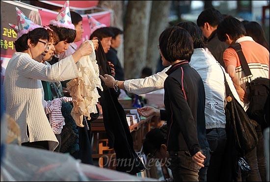 11일 오후 서울 중구 대한문 앞에서 열린 '쌍용자동차 희생자들을 돕기위한 후원 바자회'에서 이강실 한국진보연대 공동대표와 자원봉사자들이 기증된 물품을 시민들에게 보여주며 판매하고 있다