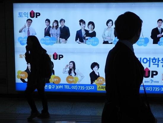 한 직장인이 서울 종각역 지하도에서 토익 관련 광고판을 바라보며 지나가고 있다.