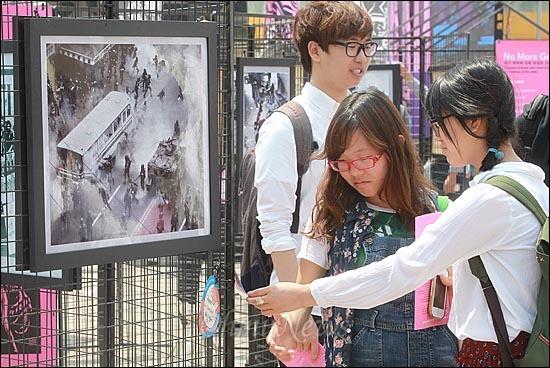 18일 오전 서울시청앞 서울광장에서 '5.18 민중항쟁 제32주년 서울 행사 기념식'이 열린 가운데, 학생들이 5.18 당시 사진자료를 둘러보고 있다.