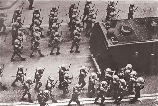 계엄군이 양손에 진압봉을 받쳐들고 시위군중을 향해 전진하고 있다.