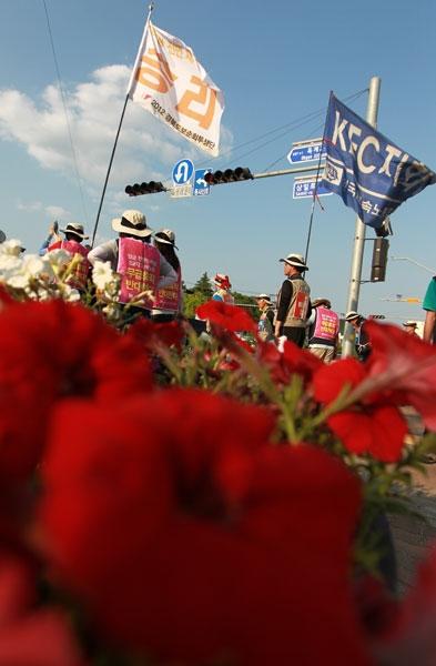 22일 오후 '민주노총 경북지역본부 2012 경북지역 도보순회투쟁'2일차 행진을 마친 민주노총 조합원들이 깃발을 들고 KEC 공장 앞으로 이동하고 있다.