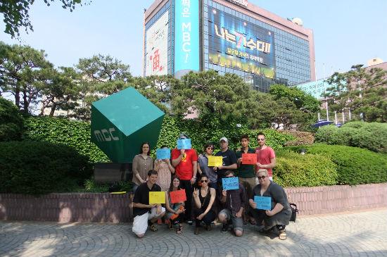시위 참가자들이 여의도 MBC 사옥 앞에서 피켓을 들고 기념 촬영을 하고 있다.