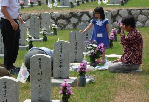 묘비 앞에서 눈시울을 젓기는 추모객과 절을 하는 아빠를 바라보는 아이
