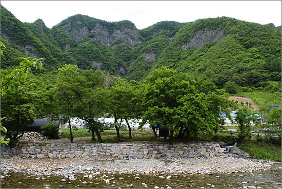 창리천. 깍아지른 듯한 바위 절벽과, 나무 그늘 아래 살짝 모습을 드러내고 있는 성황당.