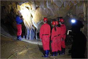 커튼형 종유석 앞에서 동굴 큐레이터의 설명을 듣고 있는 관람객들.