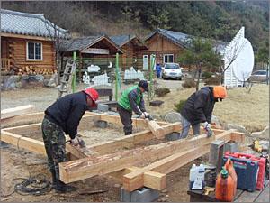 황토구들마을,통나무로 집을 짓는 과정을 배우고 있는 사람들.