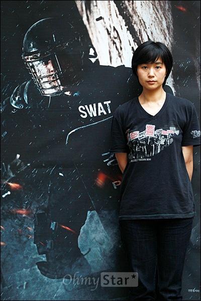 다큐멘터리 <두 개의 문>을 공동연출한 김일란 감독이 27일 오후 서울 서교동 상상마당에서 오마이스타와 인터뷰를 마친 뒤 포스터 앞에서 포즈를 취하고 있다.