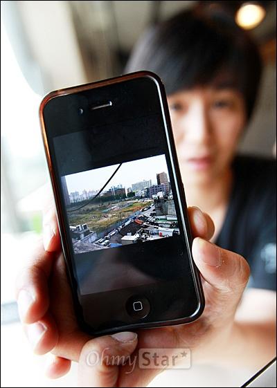 다큐멘터리 <두 개의 문>을 공동연출한 김일란 감독이 27일 오후 서울 서교동 상상마당에서 만난 오마이스타에게 용산참사 현장을 최근에 둘러본 뒤 스마트폰에 담아왔다며 풀이 자라나고 있는 현장사진을 보여주고 있다.