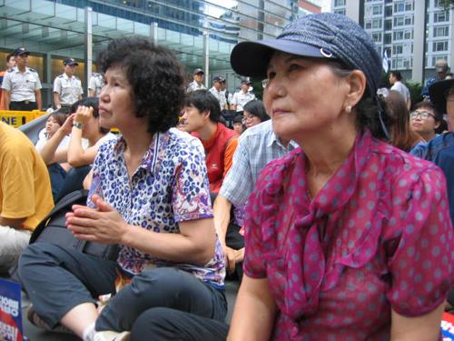지난 23일 서초동 삼성본사 건물 앞에서 열린 고(故) 황민웅씨 7주기 추모제에서 참석자가 연단의 발언을 듣고 있다.