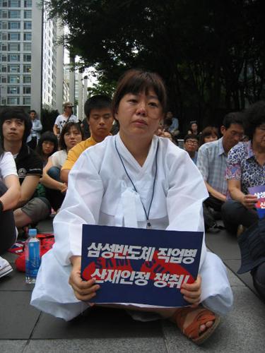 지난 23일 서초동 삼성본관 건물 앞에서 열린 고(故) 황민웅씨 7주기 추모제에서 부인 정애정씨가 추모집회에 참여하고 있다.